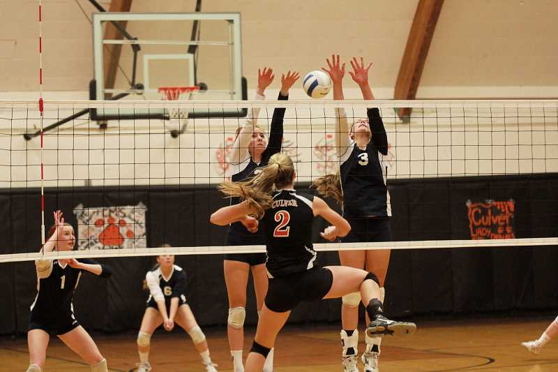 by: BILLY GATES - Madison Sprauer (left) and Amelia Grosjacques attempt to block a shot from the Bulldogs.