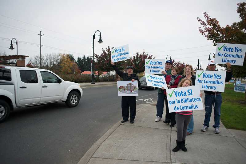 by: NEWS-TIMES PHOTO: CHASE ALLGOOD - Supporters of a library bond measure in Cornelius have been greeting rush-hour motorists on the corner outside Walgreens. Library supports come from both the Anglo and Latino communities in the city.