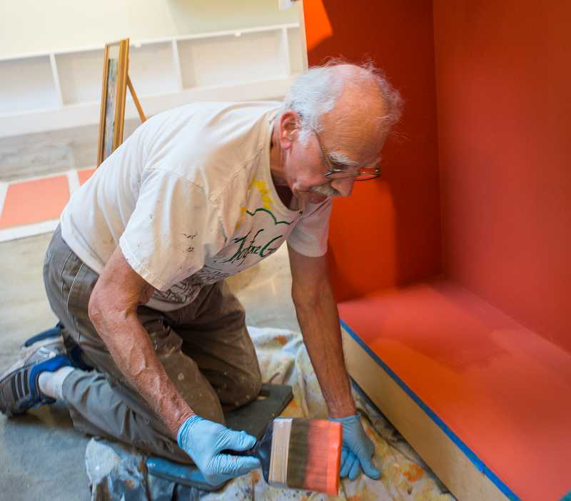 Volunteer Jerry Hoerber preps displays for new art.