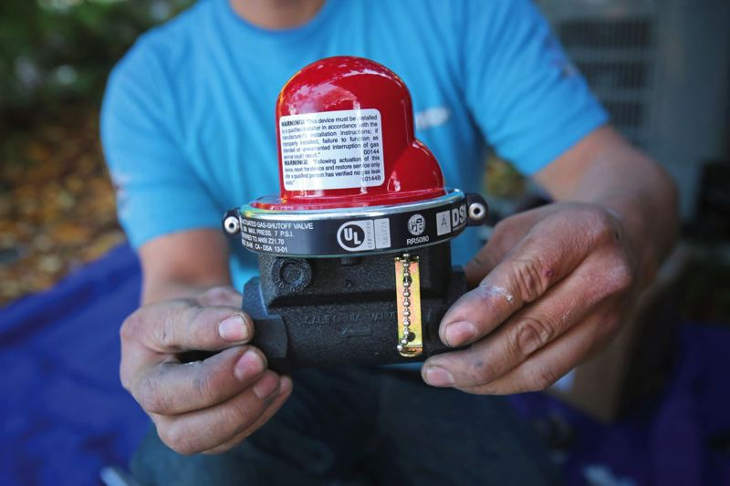 by: TRIBUNE PHOTO: JONATHAN HOUSE - Nick Perez of Earthquake Tech holds a California valve, which automatically stops the flow of natural gas during earthquakes.