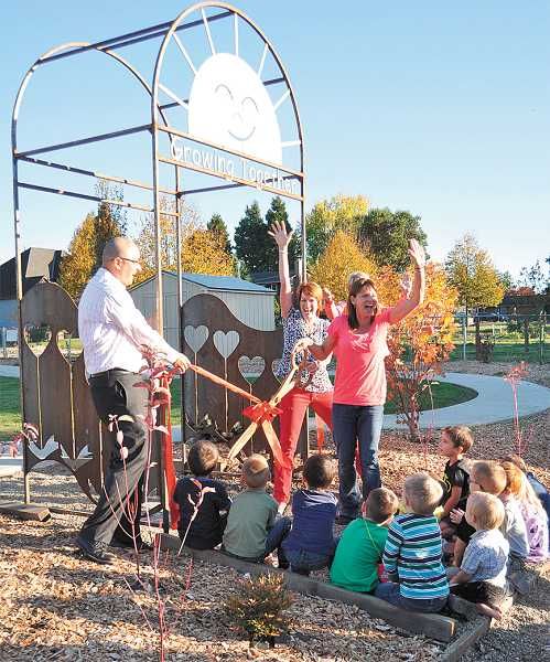 by: SUBMITTED PHOTO - Canby Community Preschool teachers (from left) Corey Lohman, Andy Fowler, Anne Bangs and former CCP teacher Julie O'Connor officially open the new play area as a group of students look on.