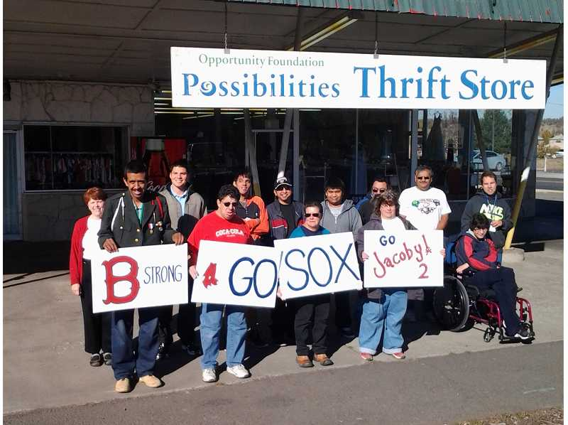 Matt Ellsbury, third from left, stands with enthusiastic employees at the Madras thrift store.