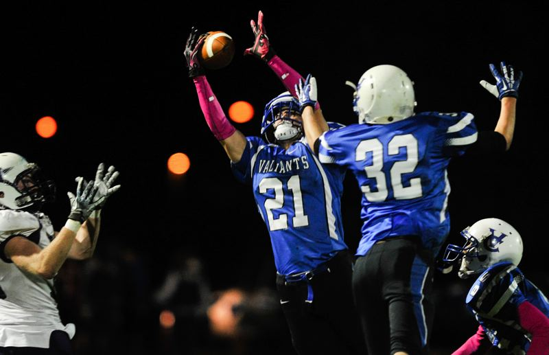 by: TIMES PHOTO: JOHN LARIVIERE  - Clay Kemper (21) of Valley Catholic nearly intercepts a pass intended for Warrenton wide receiver Bradd Lundberg late in the first quarter.  Also defending the play for the Valiants are Colin Hafferty (32) and JD Menkens (right).