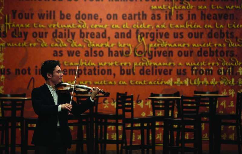 by: TIMES PHOTO: JONATHAN HOUSE - Japanese visiting violinist Kunito Nishitani warms up prior to rehearsal with the Beaverton Symphony Orchestra.
