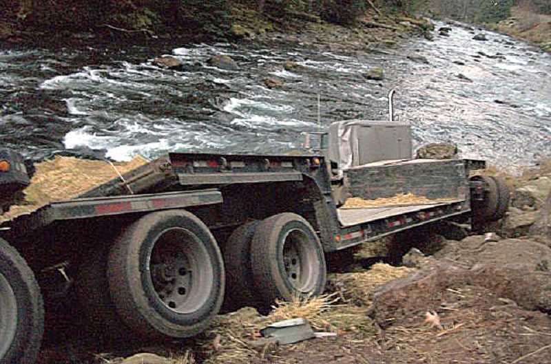 by: SUBMITTED - Mark Hess, of Woodburn, lost control of his truck, which was towing bales of hay, and crashed near the Santiam River along Highway 22 early Wednesday. The driver suffered only minor injuries.