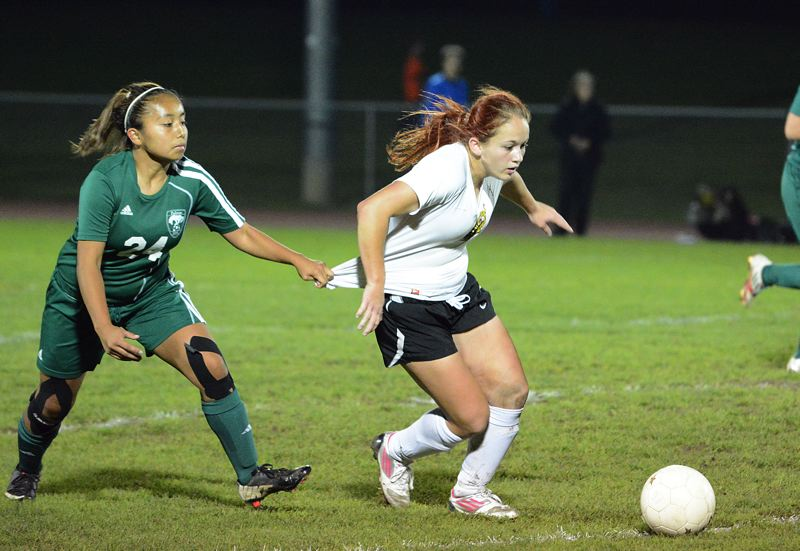 by: JOHN WILLIAM HOWARD - St. Helens sophomore Ashley Geisbers fights to pull away from a Parkrose defender during the Lions' home draw with the Broncos on Oct. 17. The team's young, but dangerous striker has been one of the biggest pieces on the team and isn't close to finished as a Lion.