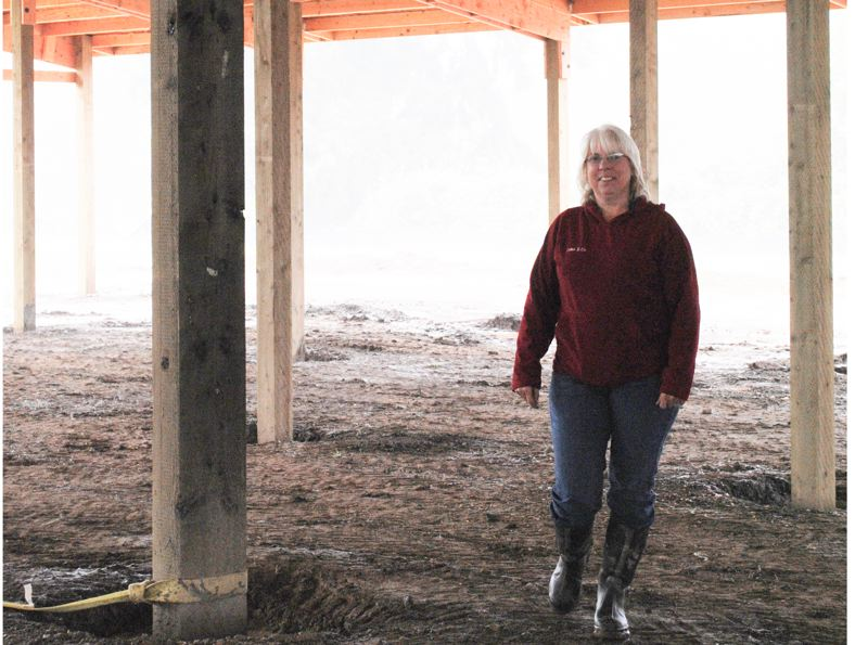 by: HILLSBORO TRIBUNE PHOTO: STEPHANIE HAUGEN - Corinne Dimick walks through the unfinished barn, imagining what the finished product will mean for her and other local riders.