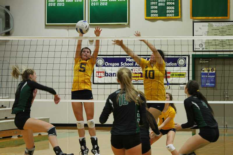 by: KORY MACGREGOR - Senior setter Abby MacGregor (5) and junior middle blocker Ana Sanchez (10) form a block during the Canby volleyball team's playoff game at Jesuit. The Cougars fell in straight sets.