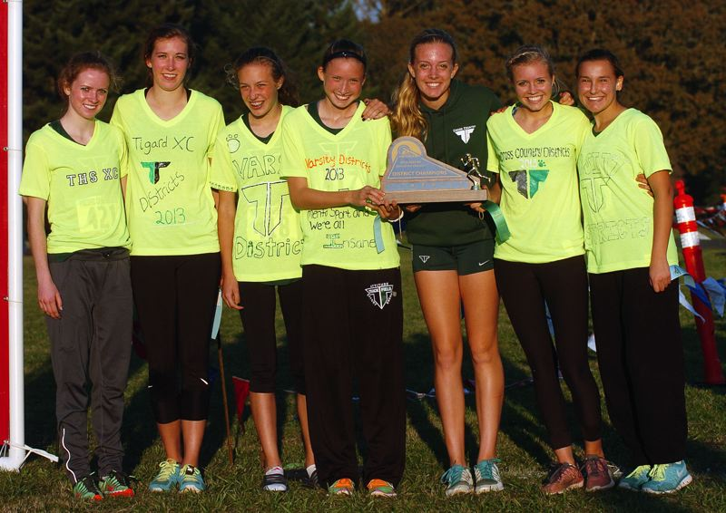 by: DAN BROOD - TIGARD'S TROPHY -- Members of the Tigard High School girls cross country team gather with the Pacific Conference championship trophy following their triumphant performance at the district meet.