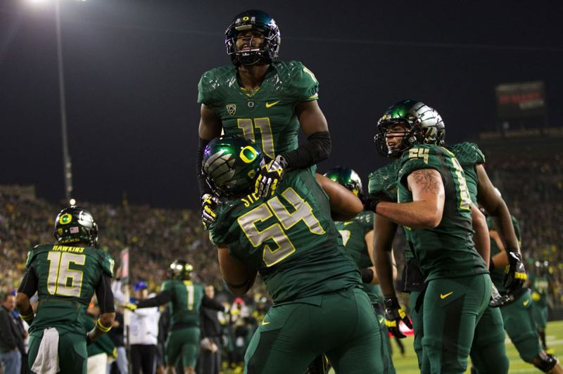 Offensive lineman Hamani Stevens gives Bralon Addison a lift after the wide receiver's touchdown against UCLA.