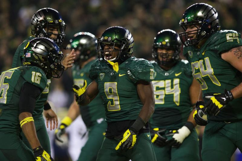 Oregon running back Byron Marshall shares a touchdown moment with teammates.