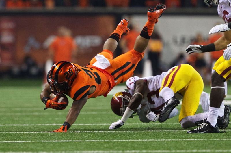 The USC defense upends Beavers running back Terron Ward.