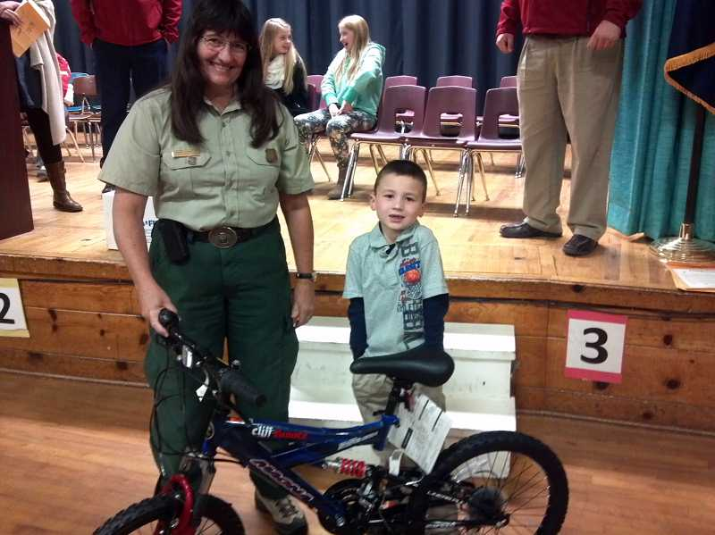 by: PHOTO CONTRIBUTED BY CCFR - Janice Lockwood with the US Forest, Service pictured with Powell Butte first grader Kaden Clevenger, winner of the bicyle drawing.
