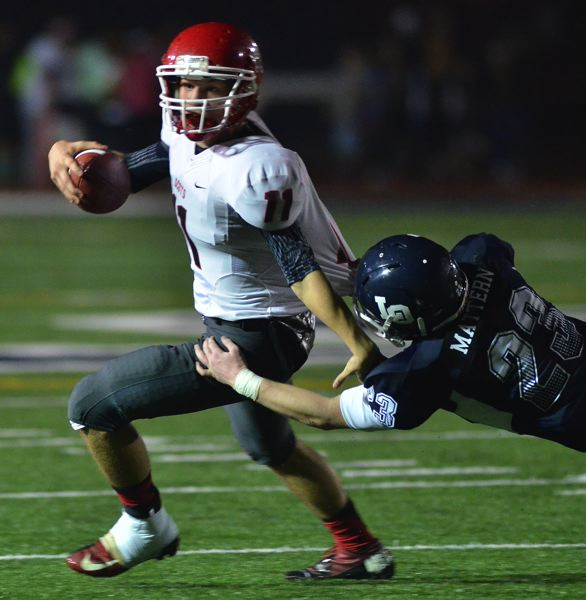 by: PAMPLIN MEDIA GROUP: VERN UYETAKE - David Douglas quarterback Hunter Davis tries to avoid a sack against Lake Oswego.