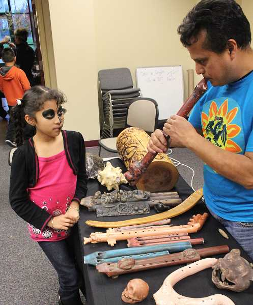 by: JEFF MCDONALD  - Samuel Becerra, 41, of Eugene, shows his daughter, Jailyn Becerra-Brigido, 9, his Pre-Columbian flutes, which were part of the Aztec and Mayan cultures.