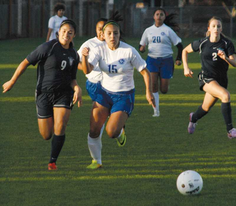 by: PHIL HAWKINS - Woodburn defender Kathya Mendez chases down a ball in the first half against the Liberty Falcons Saturday at Woodburn High School. The Bulldogs lost 5-1 in the play-in contest to mark an end to the teams 2013 season.