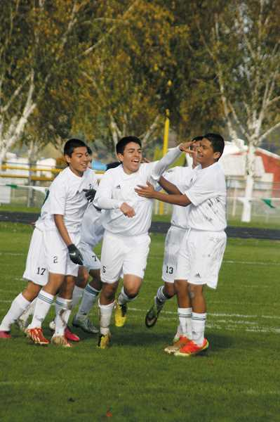 by: PHIL HAWKINS - North Marion sophomore Aaron Caballero (center) celebrates with teammates after scoring the teams lone goal in a 1-0 victory over the Ridgeview Ravens in the play-in round of the state playoffs. The victory gives the Huskies a first-round match against the No. 9 Sisters Outlaws that was scheduled for Tuesday.