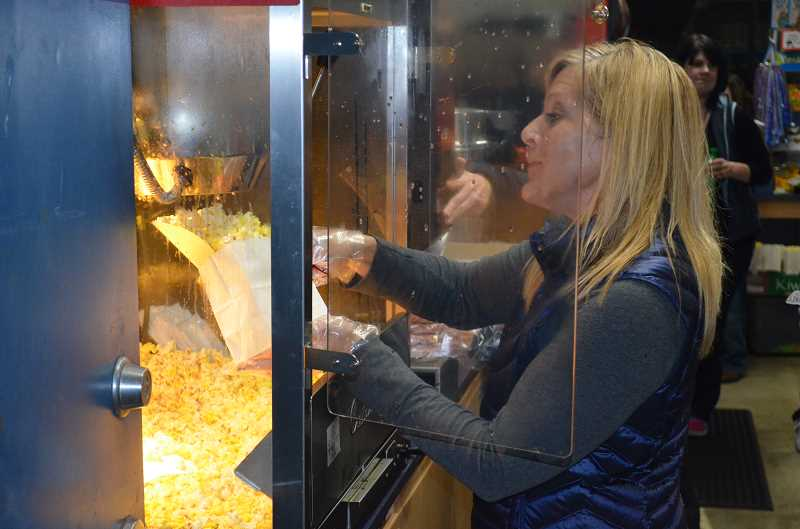 by: JEFF GOODMAN - The WHS Booster Club earns the majority of its income from selling concessions at sporting events. One volunteer, Karen Klassy, works the popcorn machine during the football game Nov. 1.