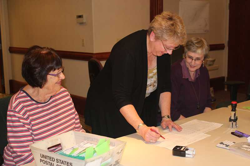 by: HOLLY M. GILL - Jefferson County Clerk Kathy Marston checks totals on Tuesday evening, as Lorelee Dendauw, left, and Sharon Hillis, right, prepare to count some of the last ballots in the election.