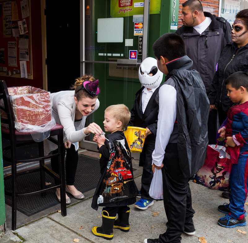 by: NEWS-TIMES PHOTO: CHASE ALLGOOD - Local merchants handed out candy to superheroes and skeletons last Thursday as part of a yearly tradition growing in popularity.