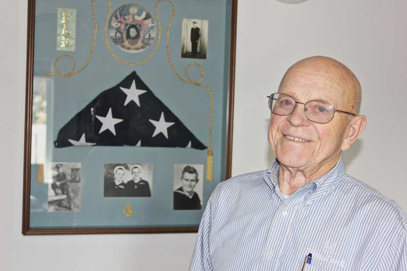by: SUSAN MATHENY/MADRAS PIONEER - Madras resident Helmer Wallan stands next to a display featuring his family's military history.