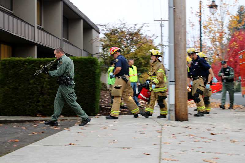 by: NEWS-TIMES PHOTOS: JOHN SCHRAG - Members of the Forest Grove Police Department escorted local firefighters into the Times-Litho building during a mock emergency response drill last Friday, while Police Chief Janie Schutz, Fire Chief Michael Kinkade and Fire Marshal Dave Nemeyer monitor events inside the building.