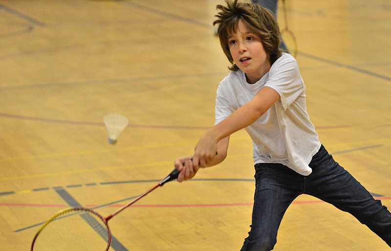 by: VERN UYETAKE - Jake Khawaja, a sixth-grader, makes a tough shot while learning to play badminton during a PE class in the Uplands Elementary School building. While the building no longer operates as a school, it offers space for some school programs.