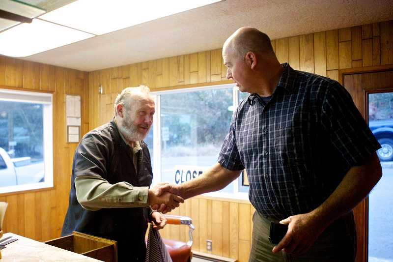 by: TIMES PHOTO: JAIME VALDEZ - Doug Luedloff of Aloha wishes Y Barber Shop owner Vern Stevens well after receiving his last hair cut from Stevens. Luedloff has gone to Stevens since high school.