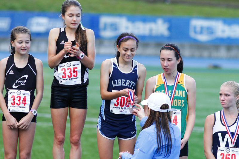 by: HILLSBORO TRIBUNE PHOTO: AMANDA MILES - Rachel Khaw receives her third-place medal following last Saturday's state cross-country meet in Eugene.