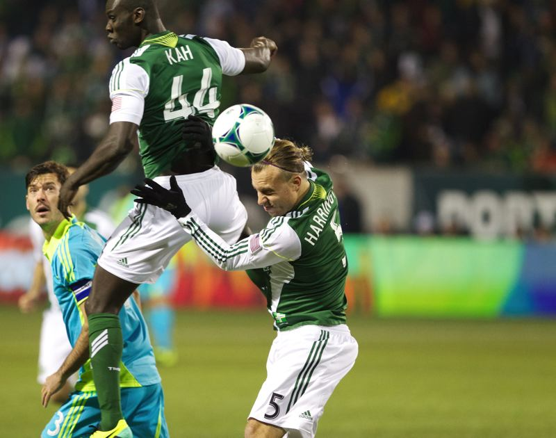 by: TRIBUNE PHOTO: JAIME VALDEZ - Portland defender Michael Harrington (right) heads the ball away in front of Timbers defender Pa Modou Kah during Thursday's win against the Seattle Sounders.