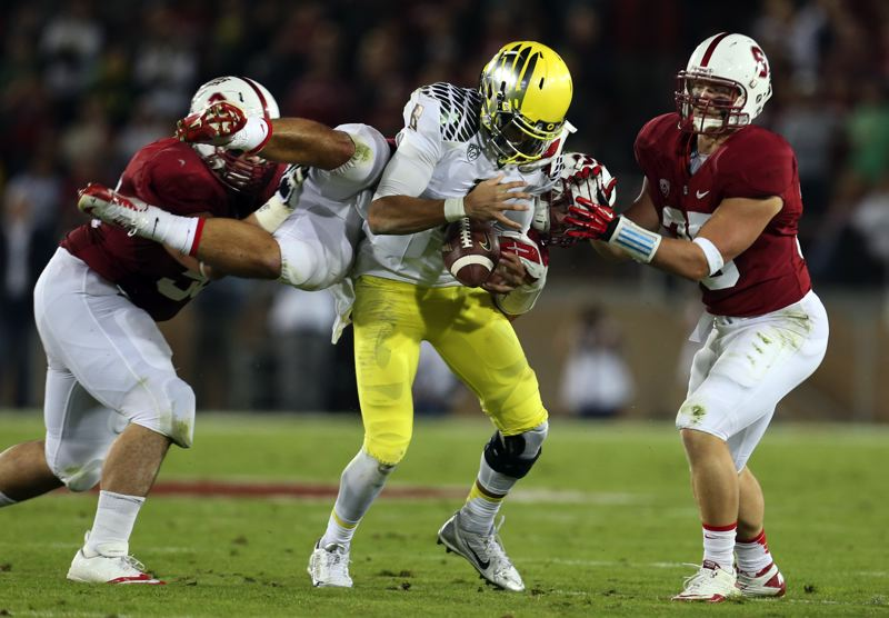 by: CHRIS PIETSCH/EUGENE REGISTER-GUARD - Oregon Ducks quarterback Marcus Mariota loses the handle on the football under pressure from the Stanford defense.