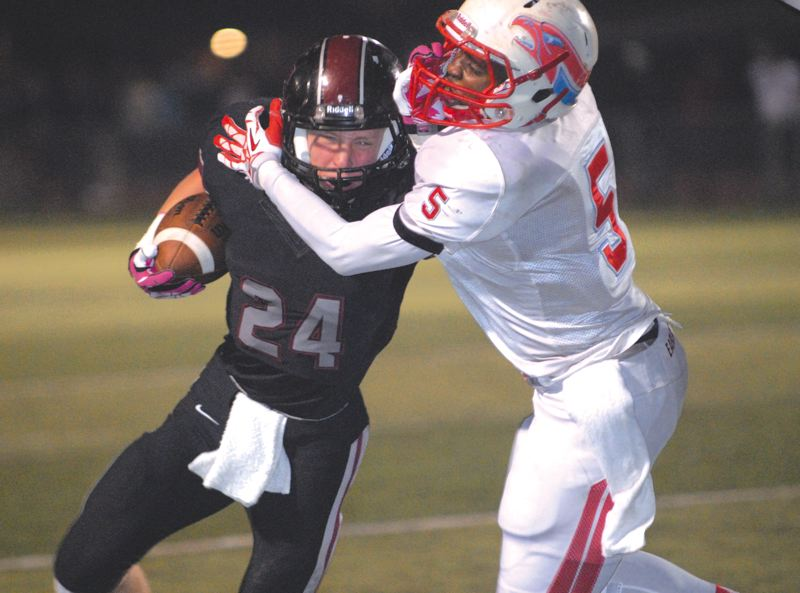by: THE OUTLOOK: DAVID BALL - Centennials Aaron Colford works to bring down Tualatin running back Connor McCullough during Fridays 14-3 first-round loss.