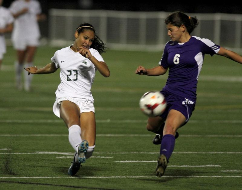 Tamia Hasan (left) sends in the ball against Weber State's Marissa Yamane.