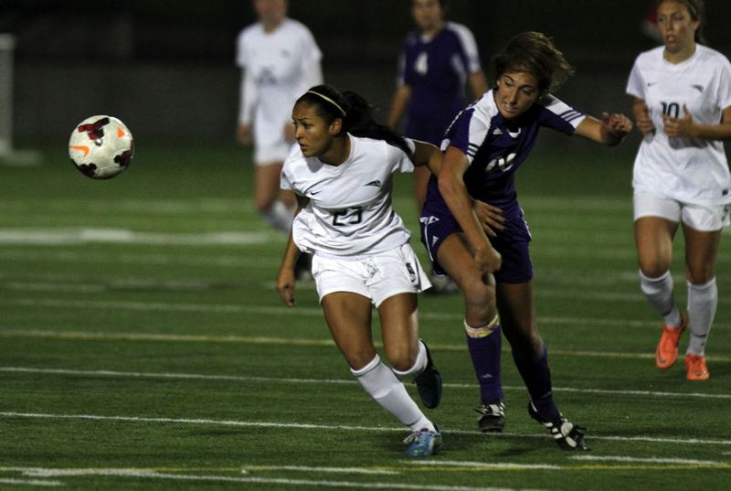 Tamia Hasan (left) of Portland State finds the ball and works to get free from the Wildcats'  defense.