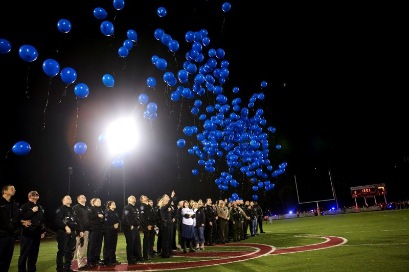 by: PHOTO BY: JAIME VALDEZ - Police officers release balloons in honor of Oregon City Police Reserve Officer Robert Libke before the start of the Oregon City Pioneers- McMinnville Grizzlies round 2 playoff game at Pioneer Stadium.