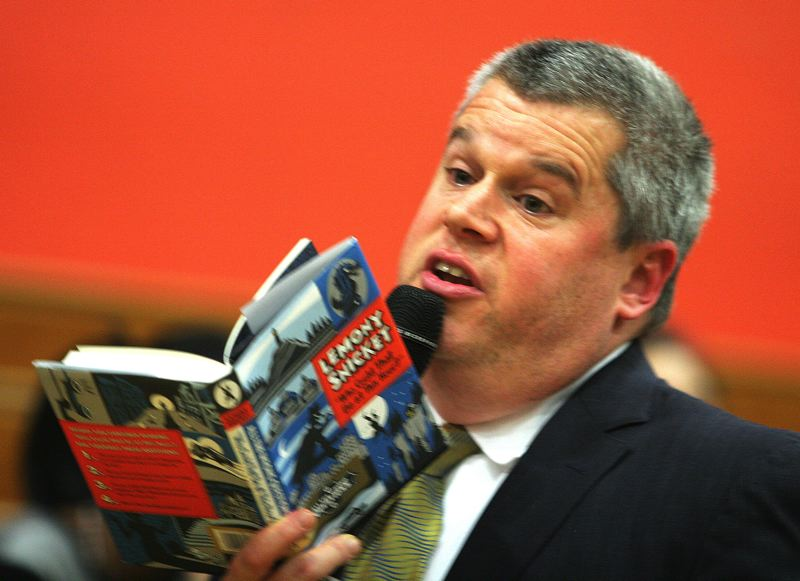 by: OUTLOOK PHOTO: JIM CLARK - Author Lemony Snicket reads from his book during a Thursday afternoon assembly at Reynolds Middle School.