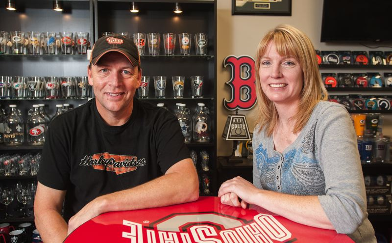 by: SPOKESMAN PHOTO: JOSH KULLA - Northwest Man Cave owners Ron Sanford (left) and Linda Zaderey recently opened up shop in Wilsonville. Their goods include a wall of team pint glasses.