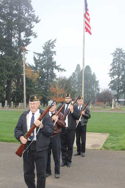 by: JEFF MCDONALD  - Members of the American Legion Color Guard stand in formation to honor veterans at Belle Passi Cemetery in Woodburn Monday.