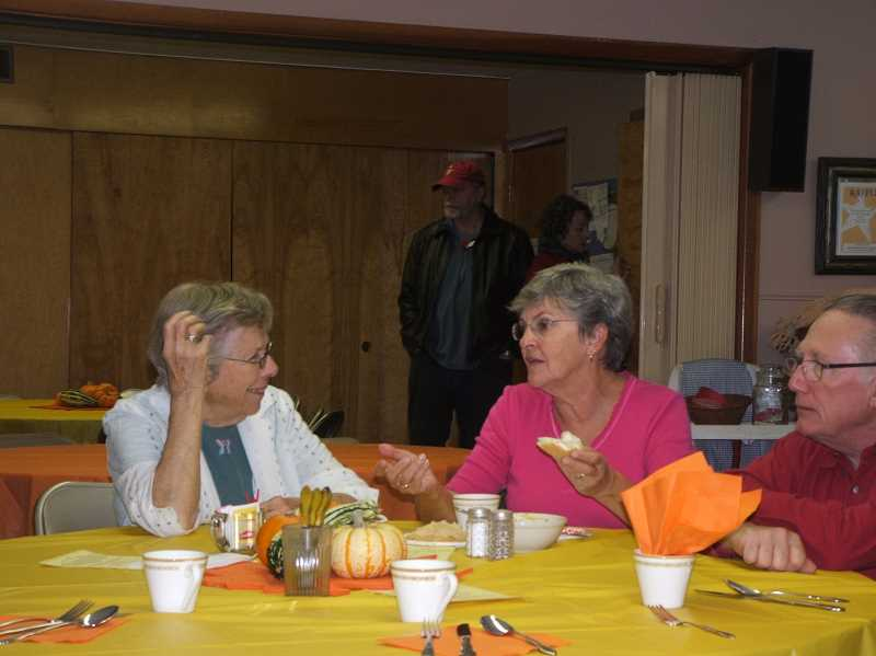 by: SUSAN VETTER - Two friends catch up over a meal at Woodburn Immanuel Lutheran Church, which hosted its annual Fall Festival on Saturday.