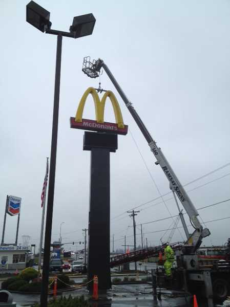 by: JEFF MCDONALD  - Crews install a new digital sign last week at McDonalds restaurant near the Woodburn Interchange Project on Highway 214.