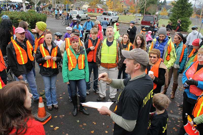 by: NEWS-TIMES PHOTO: JOHN SCHRAG - Kris Williams of Pacific Universitys outdoor recreation program gives last-minute instructions to volunteers who stood at intersections around town during the four-mile Cycle of Life event.