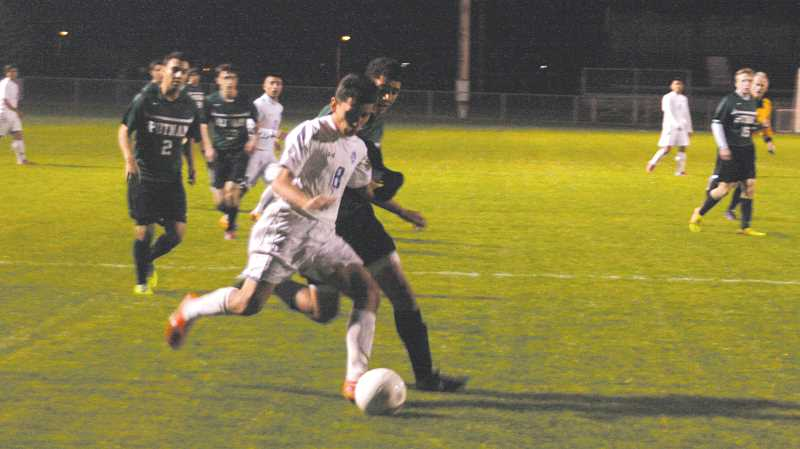 by: PHIL HAWKINS - Woodburn senior Arturo Hernandez takes the ball into the heart of the Putnam defense Saturday night. The Bulldogs constant attack led to four second-half goals, including a score by Andrew Almanzar seven minutes into the half.