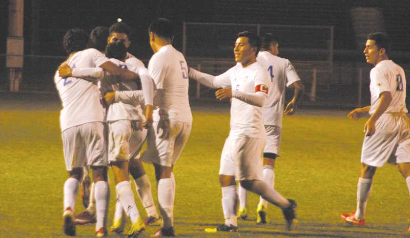 by: PHIL HAWKINS - Teammates converge on Almanzar after his goal gave Woodburn a 3-1 advantage against the Kingsmen.