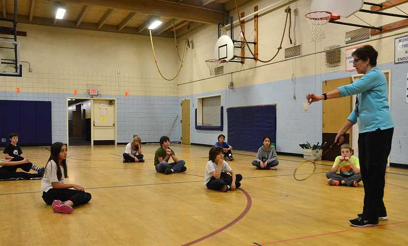 by: VERN UYETAKE - Lake Oswego Junior High PE teacher Susan Alvarez teaches a group of sixth-graders how to serve in badminton.