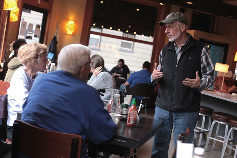 by: TRIBUNE PHOTO: JONATHAN HOUSE - Dick Satnick chats with customers at his Northwest 21st Avenue restaurant location. The goal is to nourish you, not to sell you food, he often says.
