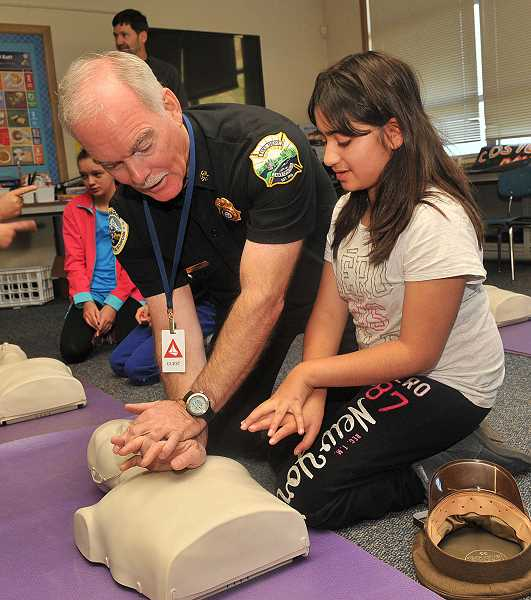 by: VERN UYETAKE - Lake Oswego Fire Department Chief Ed Wilson demonstrates the proper method of CPR to Melina Adrangi at Lake Oswego Junior High School. Wilson's goal is to have every student in Lake Oswego gain at least some knowledge of CPR.