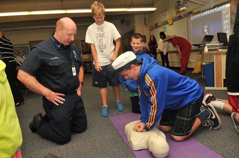 by: VERN UYETAKE - LOJHS student Chris Todd practices CPR under the expert gaze of David Smith, deputy fire marshal for Lake Oswego.