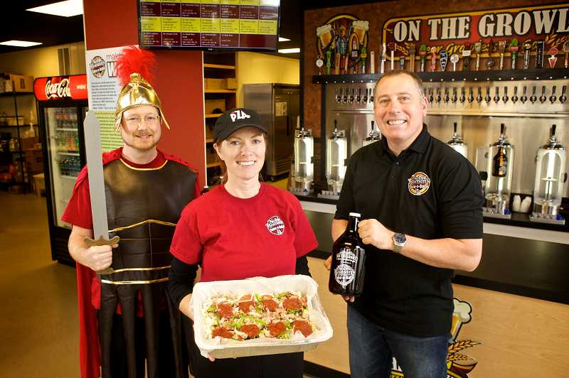 by: TIMES PHOTO: JAIME VALDEZ - Pizza artist Alan Ruff, left, dresses the part to help promote the new Noble Roman's Take-n-Bake Pizza and beer growler shop on Southwest Canyon Road with owners, Jennifer and Tim Burch.