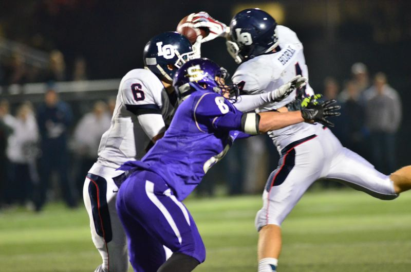 by: VERN UYETAKE - Lake Oswego's Jordan Horak secures a game-clinching interception in the final minute of last Friday's road victory against Sunset.