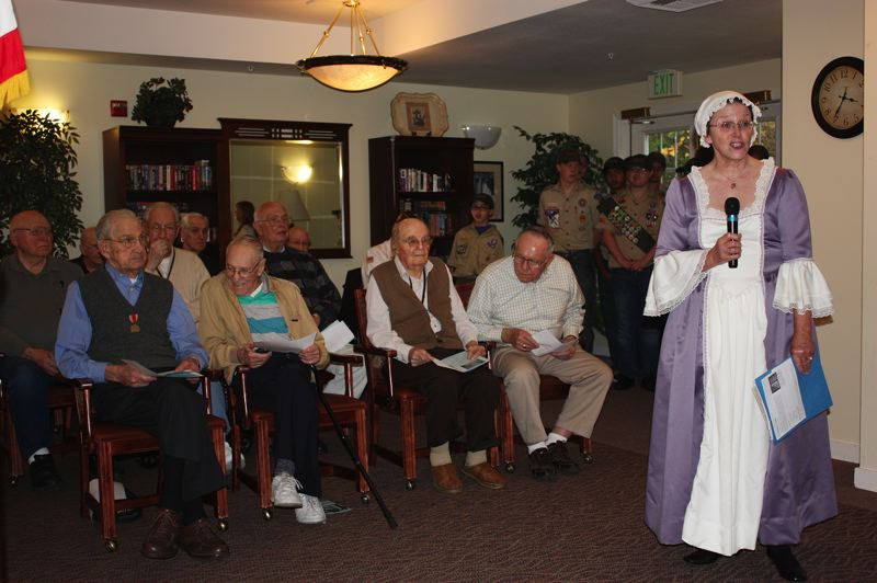 by: HILLSBORO TRIBUNE PHOTO: DOUG BURKHARDT - Eldena Vanderzanden, a member of Daughters of the American Revolution, reads the famous World War I-era poem, In Flanders Fields, at the start of Mondays ceremony honoring veterans at Avamere of Hillsboro.